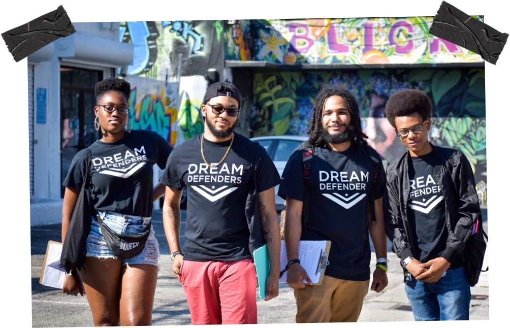 four young people wearing dream defenders tshirts pose in front of a graffiti wall