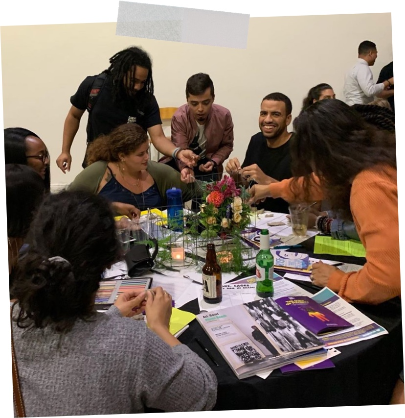 A group of smiling people sitting a table doing radical crafts